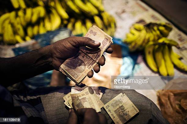 A fruit vendor counts rupee banknotes of various denominations at his stall in the old Delhi area of New Delhi India on Wednesday Sept 18 2013 The...