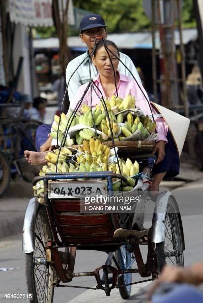 A fruit vendor is carried on a cyclo with her baskets of bananas on her way to a local market in Ho Chi Minh City 12 September 2004 Most of the...