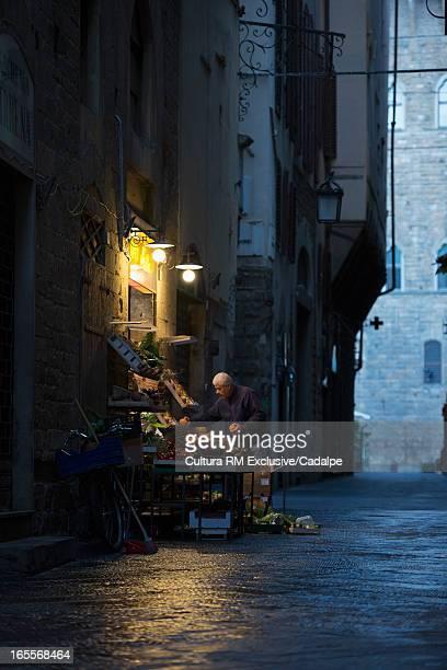 Fruit vendor on city street at night