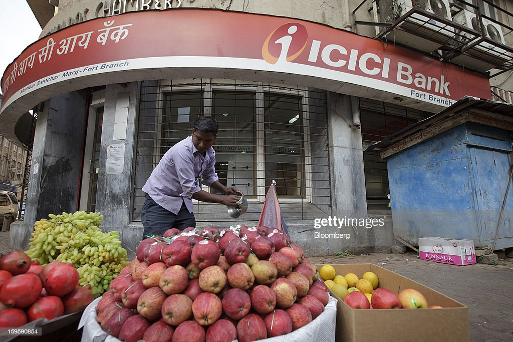 A fruit vendor organizes his stall in front of an ICICI Bank Ltd. branch in Mumbai, India, on Wednesday, Jan. 16, 2013. India's financial system has been made vulnerable by a deterioration in bank assets and a lack of capital as the economy slowed, according to the International Monetary Fund. Photographer: Kuni Takahashi/Bloomberg via Getty Images