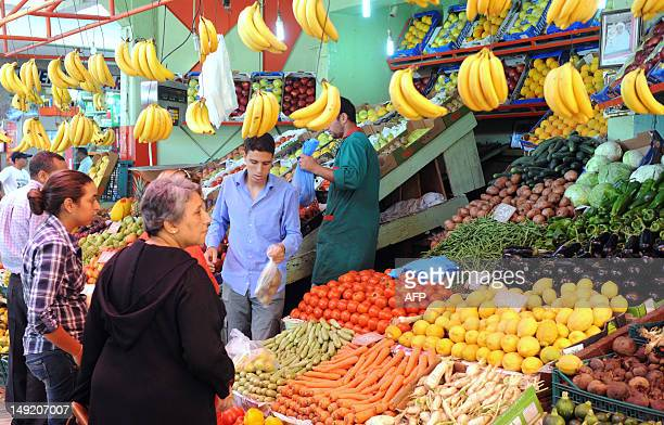 A fruit vendor serves customers at a market in Rabat on June 24 2012 The cost of primary necessities has increased in Morocco due to poor harvest AFP...