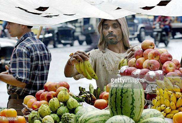 A fruit vendor stacks bananas under a plastic cover to keep the produce dry from the persistant showers in the streets of Bombay 06 September 2004...