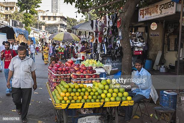 A fruit vendor tending to his stall in a busy street market