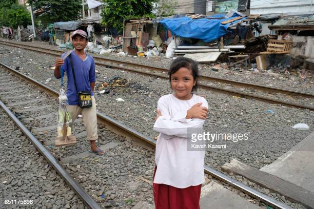 A fruit vendor walks past a young girl standing on the rairoad track in Kota City on November 25 2016 in Jakarta Indonesia The slum dwellers have...