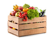 Fruits and vegetables in a wooden crate on white background.