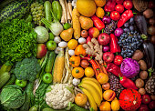Fruits and vegetables background large overhead colorful mix green to red in studio. Green, white, orange, red.