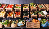 many different fresh fruits and vegetables in baskets on food market