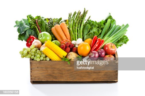 Fruits and veggies in wood box with white backdrop