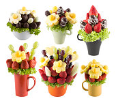 Colorful fresh fruits and chocolate on white background. Resembling a bouquet flower.