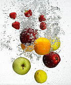 Fruits falling in water on a white background