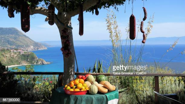 Fruits On Table By Tree Against Sea