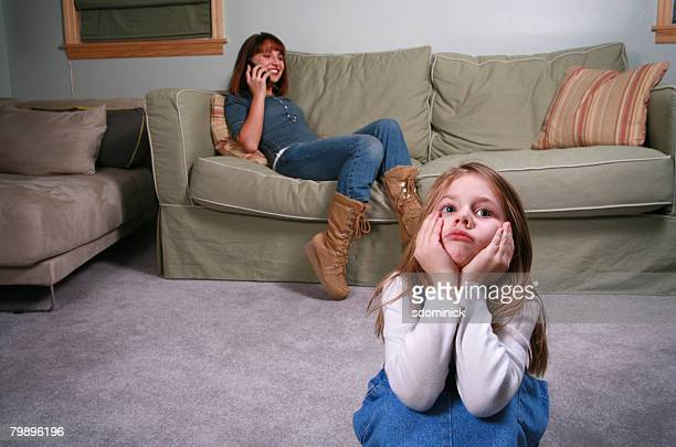 A frustrated and bored little girl sits as her babysitter/young mother chats on the phone.