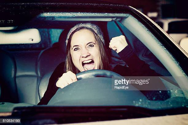 Frustrated and furious woman driver shakes fist through windshield