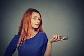 Frustrated annoyed upset woman with mobile phone standing by gray wall background