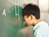 painful asian elementary schoolboy banging his head on blackboard while solving geometry problem.