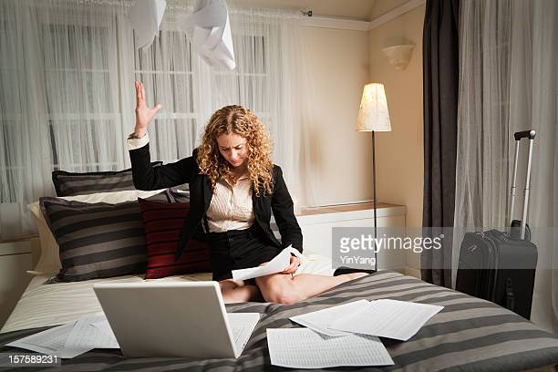 Frustrated Business Traveler Working Late in Hotel Room with Paperwork