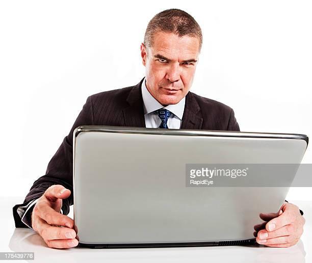 Frustriert Geschäftsmann frowns hinter laptop