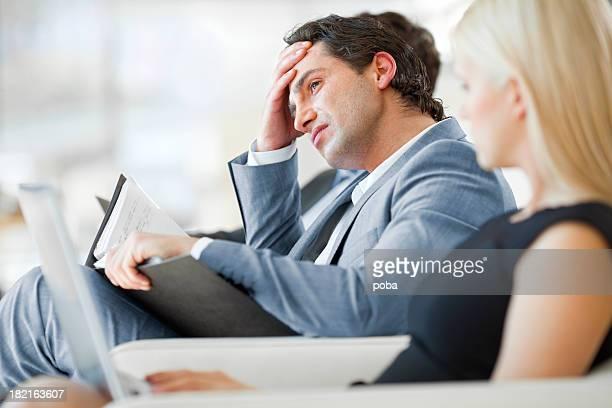 Homme d'affaires frustré un geste avec sa tête, les mains à la réunion