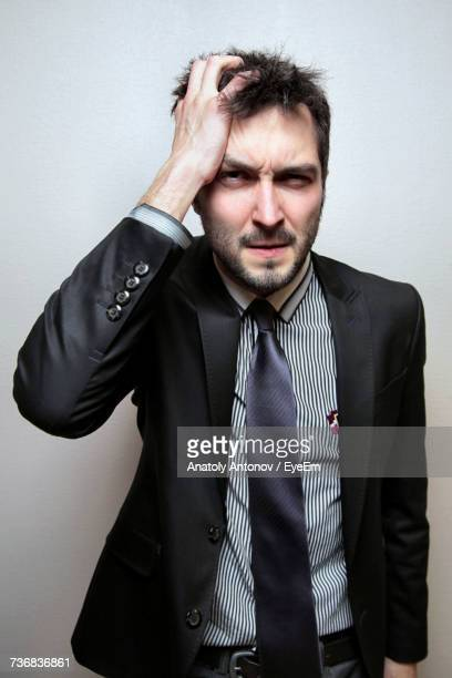 Frustrated Businessman Holding Head Against Wall