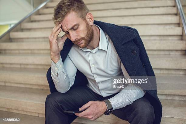 Frustrated businessman reading a text message on cell phone.