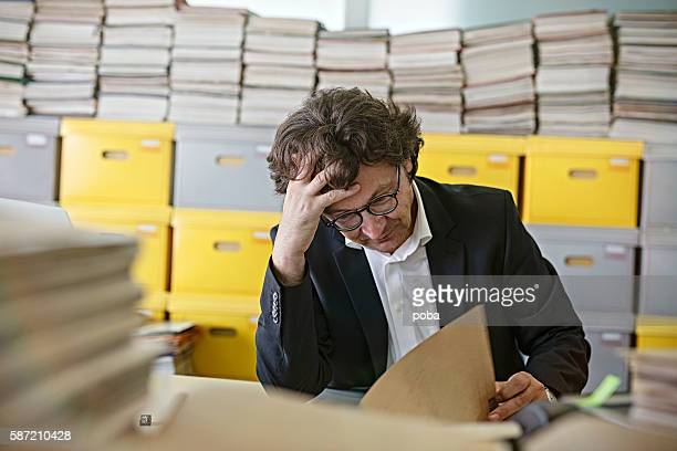 Frustrated businessman sitting at desk Overloaded With Paperwork