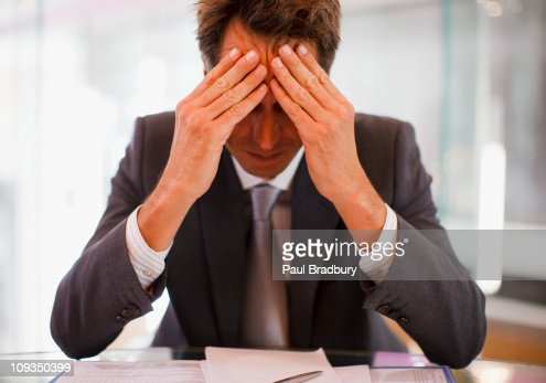Frustrated businessman sitting at desk with  head in hands : Stock Photo