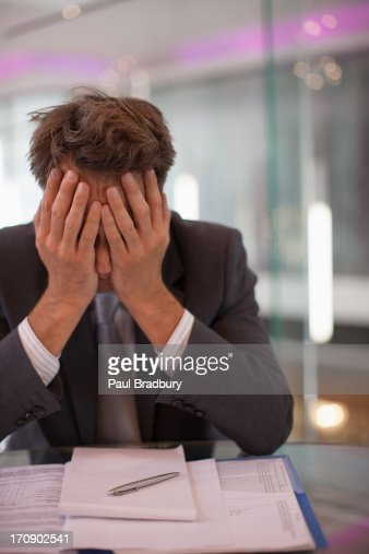 Frustrated businessman sitting at desk with  head in hands