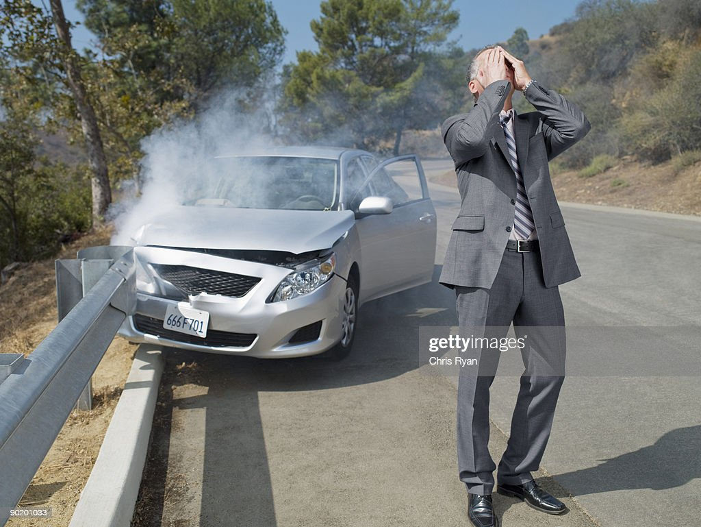 Frustrated businessman standing next to car wrecked on guardrail : Stock Photo