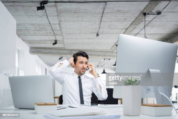 Frustrated businessman talking on phone at his desk