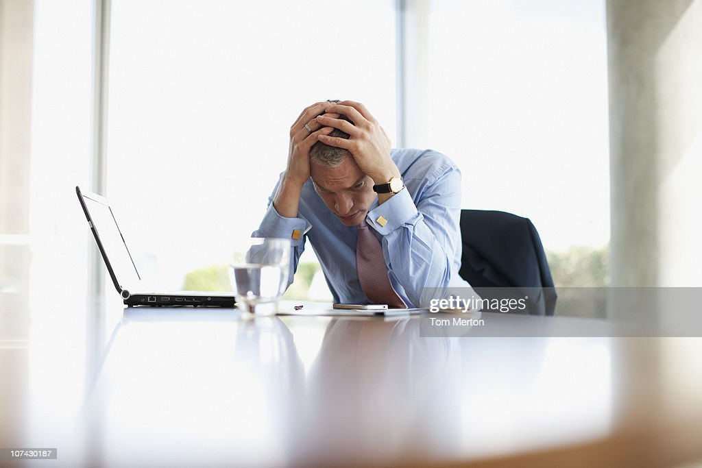 Frustrated businessman with head in hands at desk