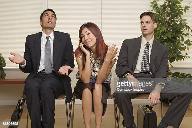 Frustrated businessmen sitting with woman talking on cell phone