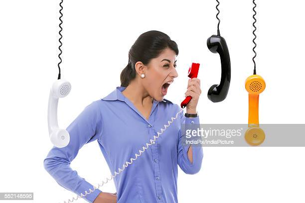 Frustrated businesswoman yelling into telephone receiver against white background