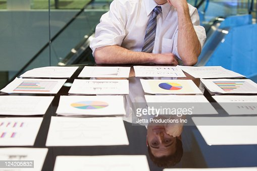 Frustrated Caucasian businessman looking at paperwork in office : Stock Photo