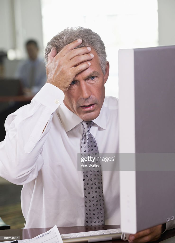 Frustrated Caucasian businessman using computer at desk