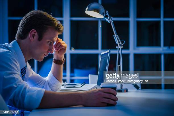 Frustrated Caucasian businessman using laptop and drinking coffee