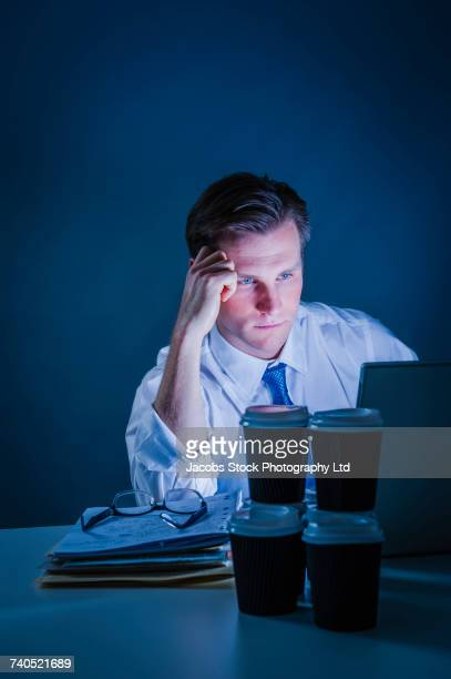 Frustrated Caucasian businessman using laptop drinking cups of coffee