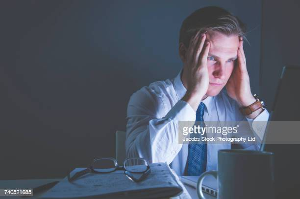 Frustrated Caucasian businessman using laptop