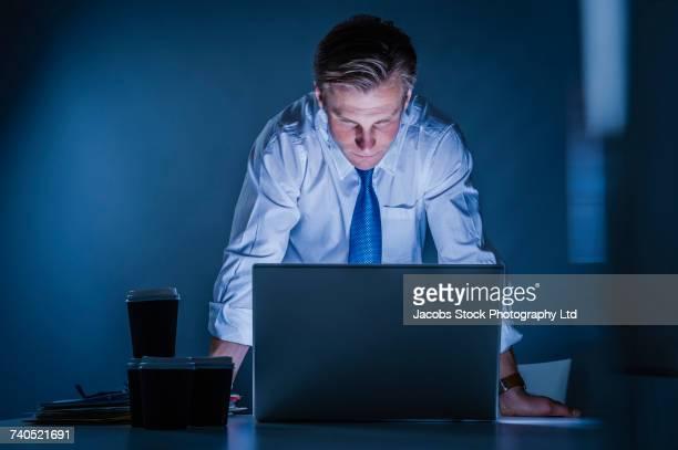 Frustrated Caucasian businessman using laptop