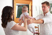 Frustrated father giving the baby to his wife