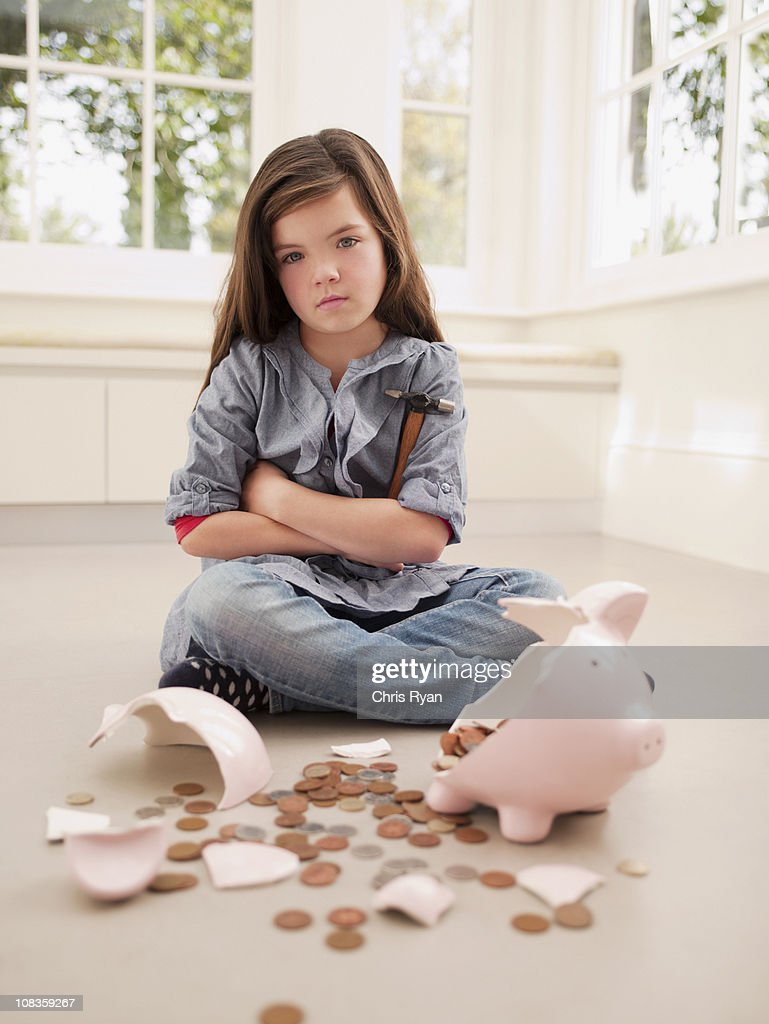 Frustrated girl sitting with broken piggy bank : Stock Photo