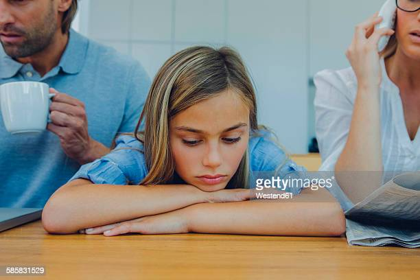 Frustrated girl with distracted parents at table