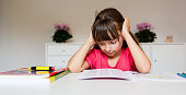 Frustrated young girl who has given up on completing her difficult homework while sitting at her desk.