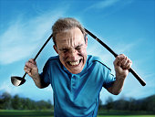 An angry, frustrated golfer bends a club over his head. Wide-angle lens distortion adds a humorous, cartoonish appearance to the subject.