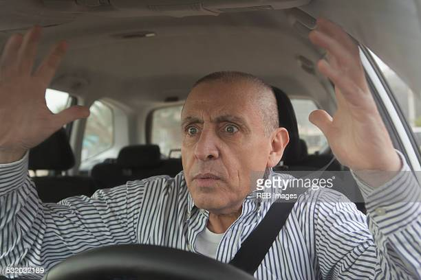 Frustrated Hispanic senior man driving car in traffic