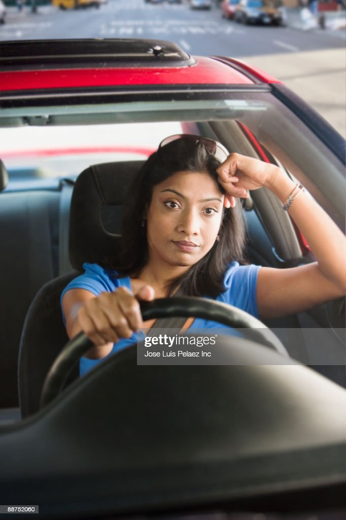 Frustrated Indian woman driving car