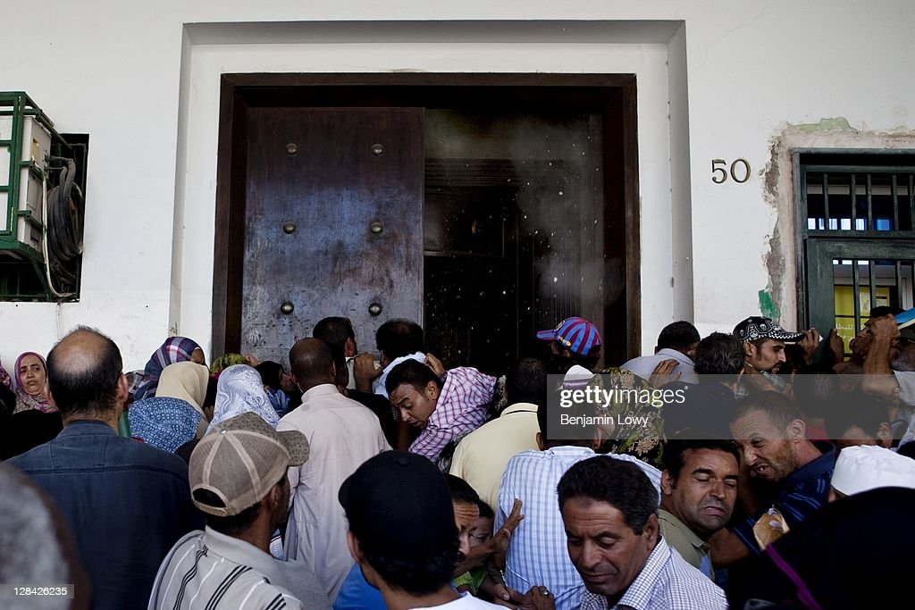 Frustrated Libyan civilians, a crowd mixed with Pro-Gaddafi and Pro-Rebel supporters, swarm outside a major Government bank in order to withdraw money on August 30 2011 in Tripoli, Libya.