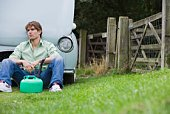 Frustrated man sitting by car that is out of gas