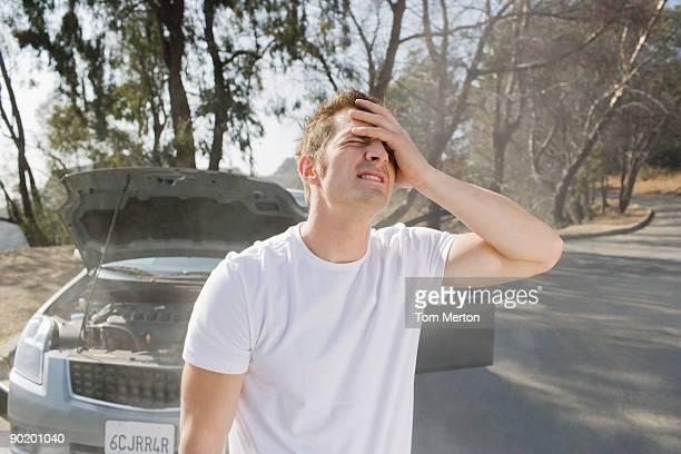 Frustrated man standing near broken down car