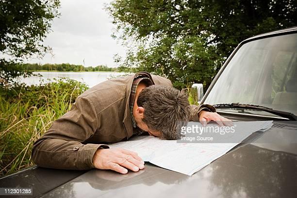 Frustrierter Mann mit Kopf auf Karte auf dem Auto-Kapuze