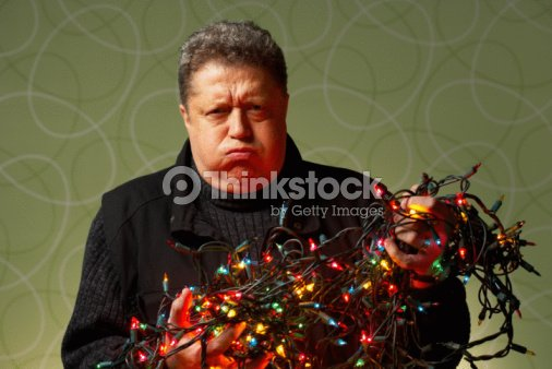 frustrated man with tangled christmas lights stock photo - Tangled Christmas Lights